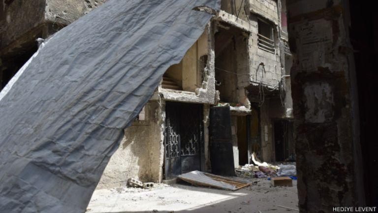 Sokaklarda keskin nişancılara karşı asılmış perdeler bulunuyor.
